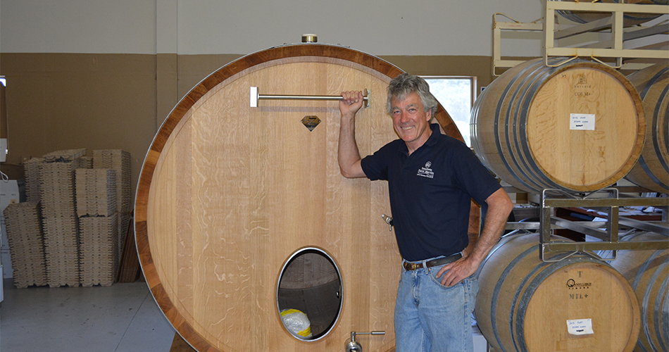 Chris Loxton with wine barrels